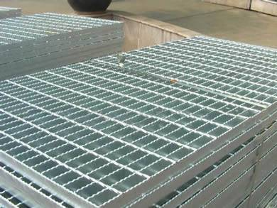 Safety serrated welded steel bar grating panels with galvanized surface treatment on the ground.