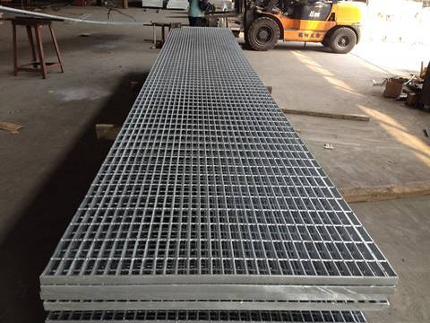 Several galvanized welded bar grating on workshop ground.